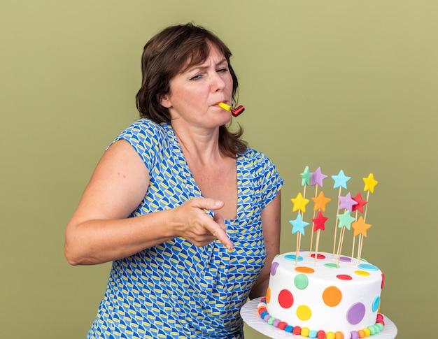 Kobieta w średnim wieku trzymająca tort urodzinowy dmuchająca gwizdkiem wskazująca palcem wskazującym na coś, co wygląda na skonfiskowane, świętuje przyjęcie urodzinowe stojące nad zieloną ścianą