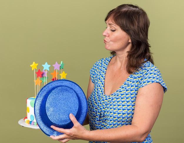 Kobieta w średnim wieku trzymająca tort urodzinowy i kapelusz imprezowy patrząca na tort z poważnym, pewnym siebie wyrazem świętująca przyjęcie urodzinowe stojące nad zieloną ścianą