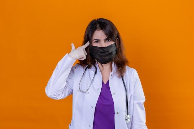 Kobieta w średnim wieku ubrana w biały płaszcz w czarnej ochronnej masce na twarz i ze stetoskopem wskazująca świątynię z palcem koncentrującym się mocno na pomyśle z poważnym spojrzeniem stojącym nad iso