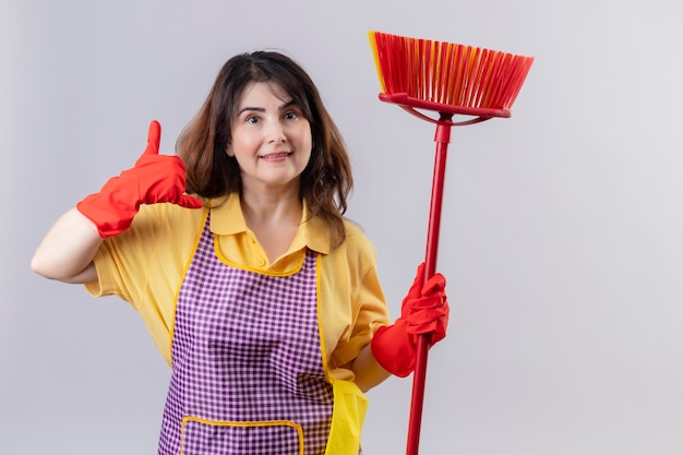 Kobieta w średnim wieku ubrana w fartuch i gumowe rękawiczki stojąca z mopem, dzwoniąc do mnie gestem