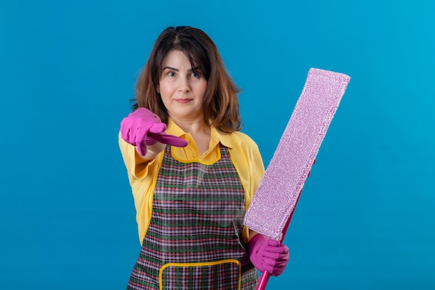 Kobieta w średnim wieku ubrana w fartuch i rękawice gumowe trzymając mop wskazujący palcem wskazującym