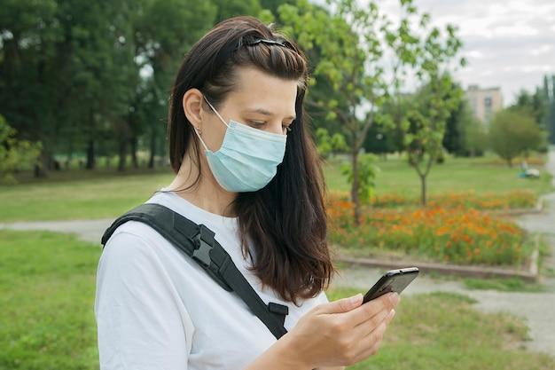 Kobieta w średnim wieku ubrana w maskę medyczną na zewnątrz