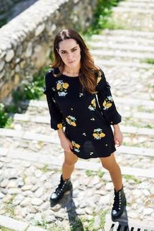 Kobieta w średnim wieku ubrana w sukienkę w kwiaty w miejskich krokach.
