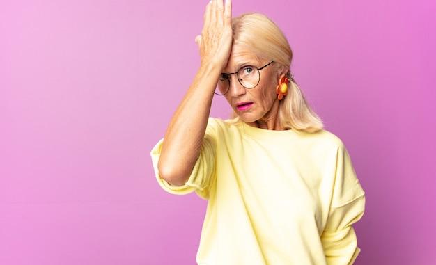 """Kobieta w średnim wieku unosząca dłoń do czoła, myśląc """"ups"""" po popełnieniu głupiego błędu lub przypomnieniu sobie"""