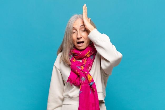 """Kobieta w średnim wieku unosząca dłoń do czoła, myśląca """"ups"""", po popełnieniu głupiego błędu lub przypomnienia sobie, głupia"""
