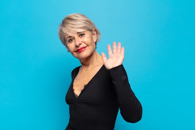 Kobieta w średnim wieku uśmiecha się radośnie i radośnie, machając ręką i pozdrawiając cię lub żegnając się