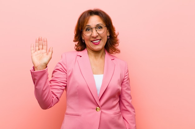 Kobieta w średnim wieku uśmiecha się radośnie i wesoło, macha ręką, wita i wita lub żegna różową ścianę