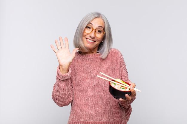 Kobieta w średnim wieku uśmiecha się radośnie i wesoło, macha ręką, wita i wita lub żegna się z koncepcją azjatyckiego jedzenia
