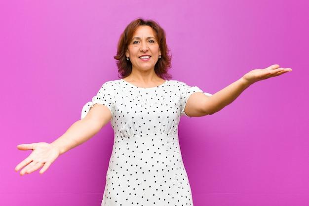 Kobieta w średnim wieku uśmiecha się radośnie, przytulając się ciepło i przyjaźnie, czując się szczęśliwa i urocza na tle fioletowej ściany