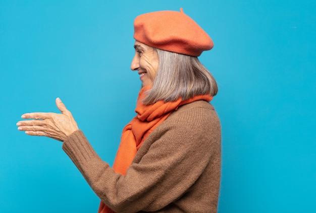 Kobieta w średnim wieku uśmiecha się, wita cię i podaje uścisk dłoni, aby zamknąć udaną transakcję, koncepcja współpracy