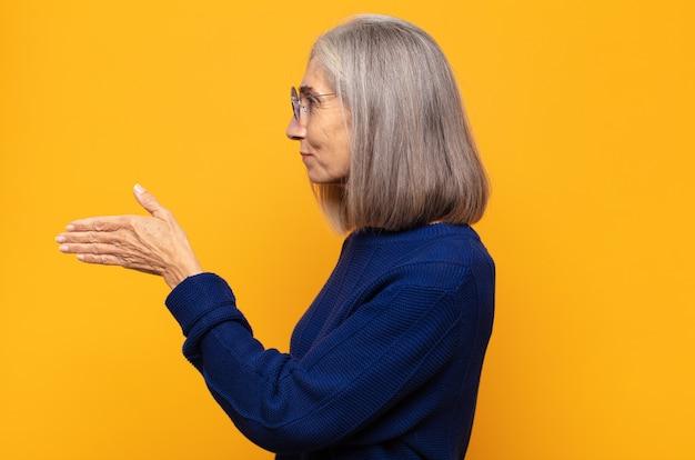 Kobieta w średnim wieku uśmiecha się, wita i oferuje uścisk dłoni, aby sfinalizować udaną transakcję, koncepcja współpracy