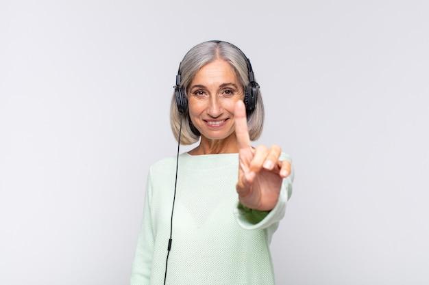 Kobieta w średnim wieku, uśmiechając się dumnie na białym tle