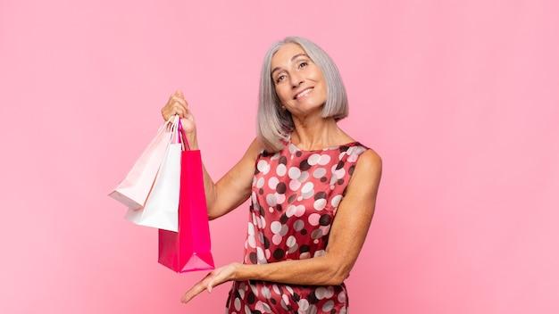 Kobieta w średnim wieku, uśmiechając się radośnie, czując się szczęśliwa i pokazując koncepcję w przestrzeni kopii z dłoni z torby na zakupy