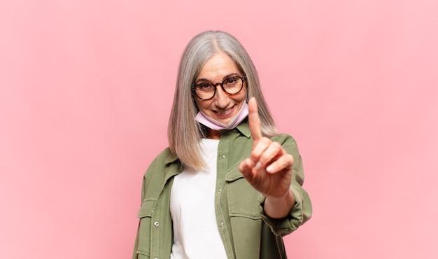 Kobieta w średnim wieku, uśmiechnięta dumnie i pewnie, wykonująca triumfalnie pozę numer jeden, czująca się jak przywódczyni