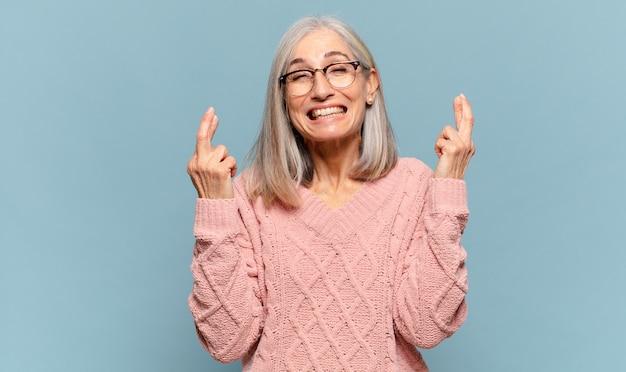 Kobieta w średnim wieku uśmiechnięta i niespokojnie krzyżująca oba palce, zmartwiona i życząca lub mająca nadzieję na szczęście
