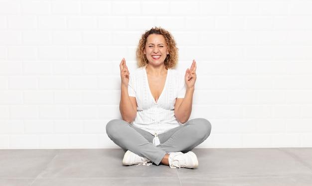 Kobieta w średnim wieku uśmiechnięta i niespokojnie ściskająca oba palce, zmartwiona i życząca lub licząca na szczęście
