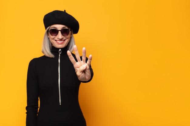 Kobieta w średnim wieku, uśmiechnięta i przyjazna, pokazująca cyfrę cztery lub czwarte z ręką do przodu, odliczająca w dół