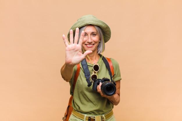 Kobieta w średnim wieku, uśmiechnięta i przyjazna, pokazująca cyfrę pięć lub piąty z ręką do przodu, odliczająca