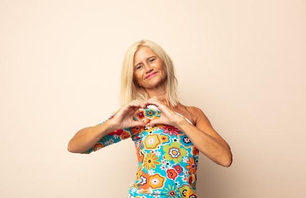 Kobieta w średnim wieku uśmiechnięta i szczęśliwa, słodka, romantyczna i zakochana, nadająca kształt serca obiema rękami