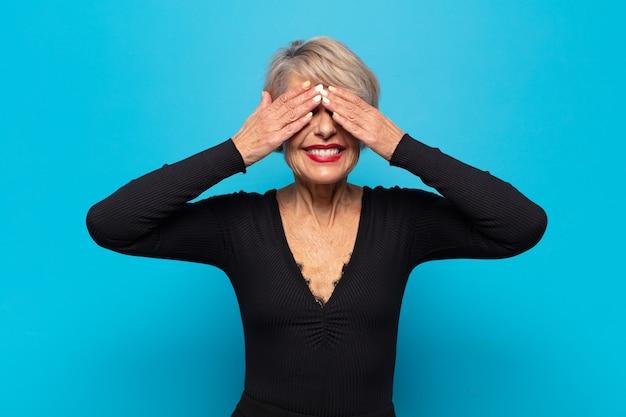 Kobieta w średnim wieku uśmiechnięta i szczęśliwa, zasłaniająca oczy obiema rękami i czekająca na niewiarygodną niespodziankę