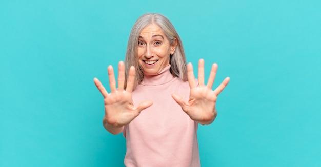 Kobieta w średnim wieku uśmiechnięta i wyglądająca przyjaźnie, pokazująca cyfrę dziesiątą lub dziesiątą z ręką do przodu, odliczając w dół