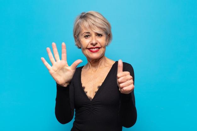 Kobieta w średnim wieku uśmiechnięta i wyglądająca przyjaźnie, pokazująca numer sześć lub szósty z ręką do przodu, odliczając w dół
