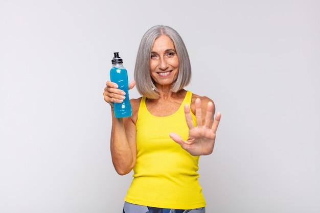Kobieta w średnim wieku uśmiechnięta i wyglądająca przyjaźnie, pokazująca ręką piątą lub piątą