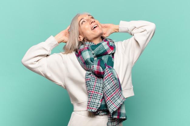 Kobieta w średnim wieku uśmiechnięta i zrelaksowana, zadowolona i beztroska, śmiejąca się pozytywnie i mrożąca krew w żyłach