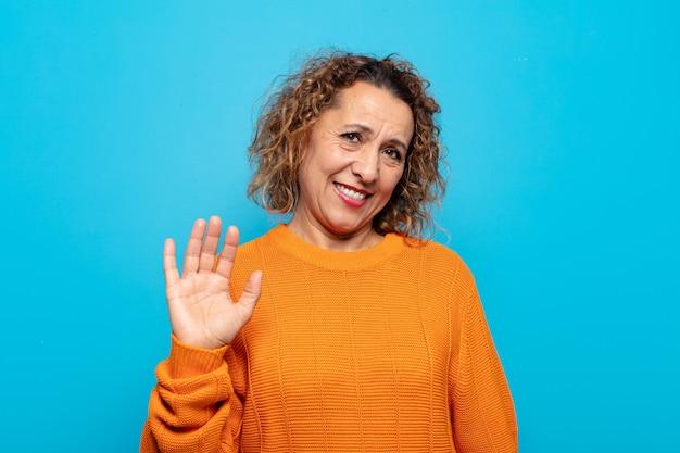 Kobieta w średnim wieku uśmiechnięta radośnie i radośnie, machająca ręką, witająca cię i pozdrawiająca lub żegnająca się