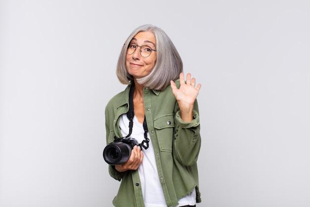 Kobieta w średnim wieku uśmiechnięta radośnie i radośnie, machająca ręką, witająca i pozdrawiająca lub żegnająca. koncepcja fotografa