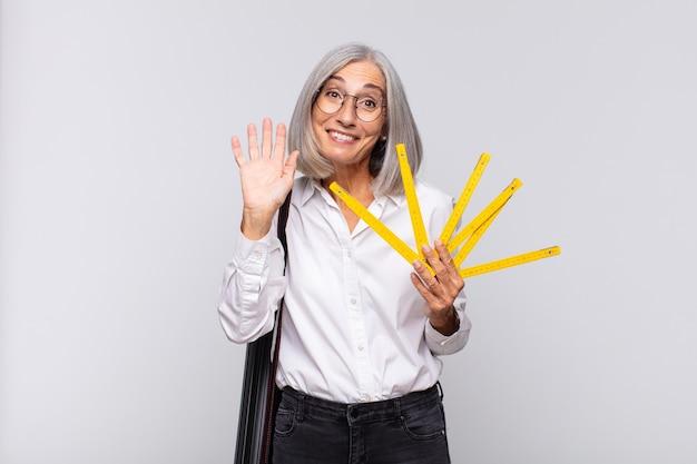 Kobieta w średnim wieku, uśmiechnięta radośnie i wesoło, machająca ręką, witająca i witająca lub żegnająca się. koncepcja architekta