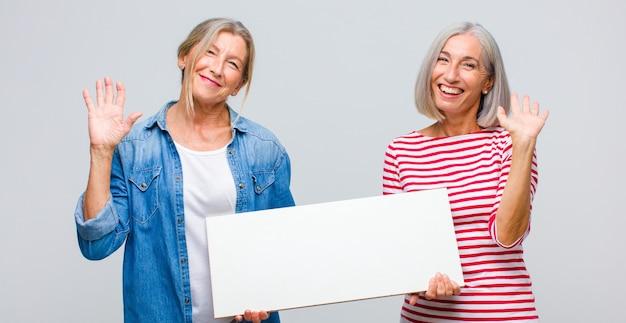 Kobieta w średnim wieku, uśmiechnięta radośnie i wesoło, machająca ręką, witająca i witająca lub żegnająca się