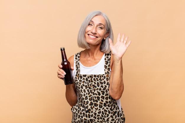 Kobieta w średnim wieku uśmiechnięta radośnie i wesoło, machająca ręką