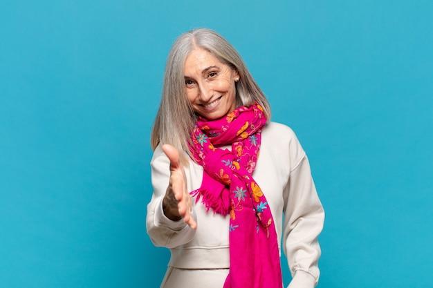Kobieta w średnim wieku uśmiechnięta, wyglądająca na szczęśliwą, pewną siebie i przyjazną, oferująca uścisk dłoni w celu zawarcia transakcji, współpracująca