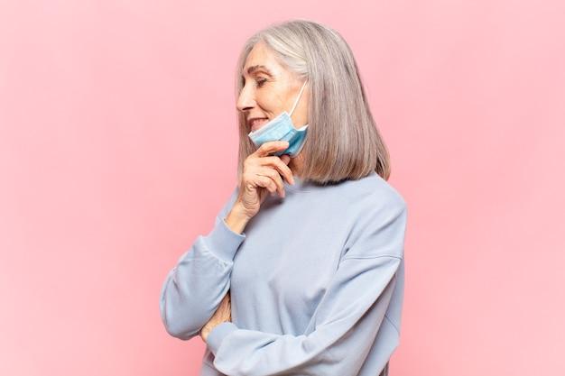 Kobieta w średnim wieku uśmiechnięta ze szczęśliwym, pewnym siebie wyrazem twarzy z ręką na brodzie, zastanawiająca się i patrząca w bok