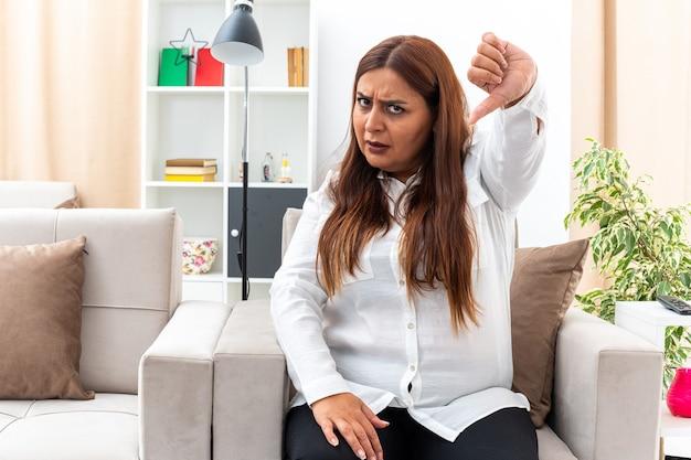 Kobieta w średnim wieku w białej koszuli i czarnych spodniach z poważną twarzą pokazującą kciuki w dół, siedząca na krześle w jasnym salonie
