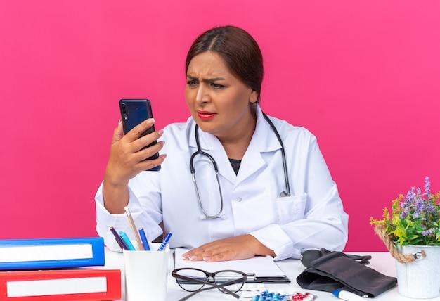 Kobieta w średnim wieku w białym fartuchu ze stetoskopem trzymająca smartfona patrząca na niego z poważną miną niezadowoloną siedzącą przy stole z biurowymi folderami na różowym tle