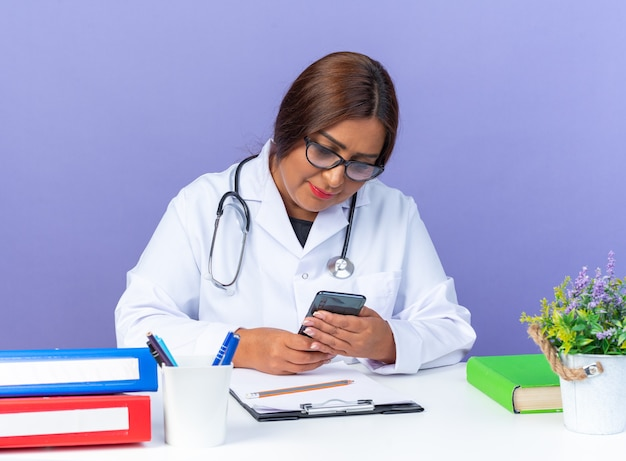 Kobieta w średnim wieku w białym fartuchu ze stetoskopem w okularach trzymająca smartfona patrząca na niego z uśmiechem na twarzy siedzącej przy stole nad niebieską ścianą
