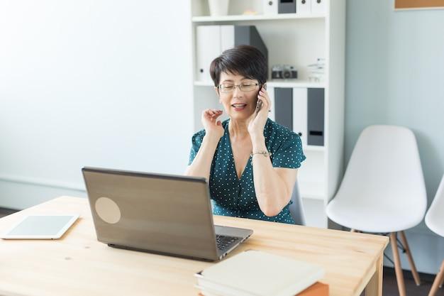 Kobieta w średnim wieku w biurze pracy z laptopem i dokonanie