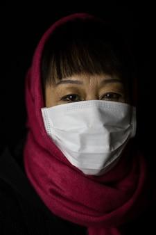Kobieta w średnim wieku w bordowym hidżabie, ubrana w maskę