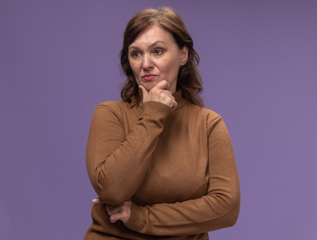 Kobieta w średnim wieku w brązowym golfie patrząc na bok z poważną twarzą z ręką na brodzie myśli stojącej nad fioletową ścianą