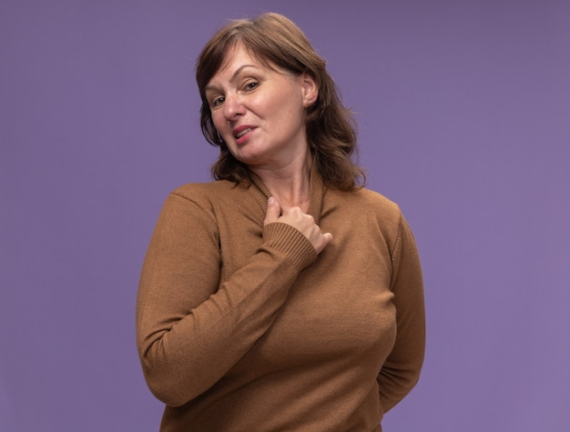 Kobieta w średnim wieku w brązowym golfie wyglądająca na zirytowaną i zirytowaną dotykającą szyi stojącej nad fioletową ścianą