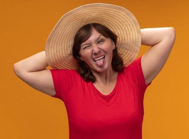 Kobieta w średnim wieku w czerwonej koszulce i kapeluszu letnim szczęśliwy i radosny wystający język stojący nad pomarańczową ścianą