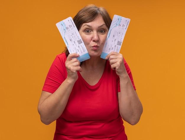 Kobieta w średnim wieku w czerwonej koszulce trzyma bilety lotnicze szczęśliwa i zdziwiona stojąc nad pomarańczową ścianą