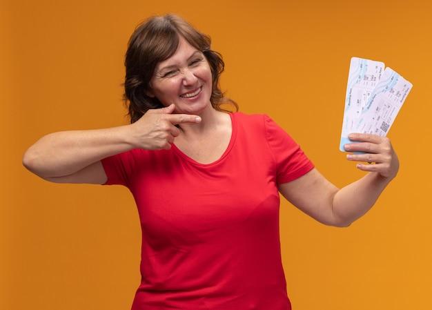 Kobieta w średnim wieku w czerwonej koszulce trzyma bilety lotnicze wskazując palcem wskazującym na nich szczęśliwa i pozytywnie uśmiechnięta stojąca nad pomarańczową ścianą