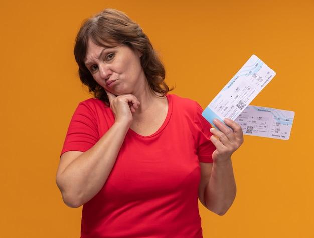 Kobieta w średnim wieku w czerwonej koszulce trzyma bilety lotnicze z wyrazem sceptyka stojąc nad pomarańczową ścianą