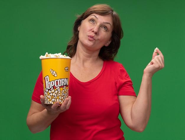 Kobieta w średnim wieku w czerwonej koszulce trzyma wiadro z popcornem patrząc zdziwiona stojąc nad zieloną ścianą