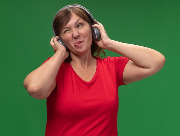 Kobieta w średnim wieku w czerwonej koszulce ze słuchawkami wystający język szczęśliwa i radosna stojąca nad zieloną ścianą