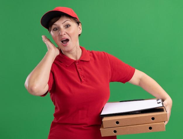 Kobieta w średnim wieku w czerwonym mundurze i czapce trzymająca pudełka po pizzy i schowek z pustymi stronami patrząc z przodu zdezorientowana i zaskoczona stojąc nad zieloną ścianą