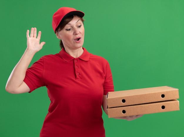 Kobieta w średnim wieku w czerwonym mundurze i czapce trzymająca pudełka po pizzy patrząc na nich szczęśliwa i podekscytowana z podniesioną ręką stojącą nad zieloną ścianą